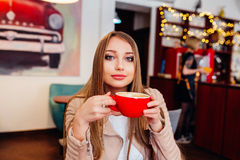 Beautiful young woman with a red cup of coffee at a cafe. Woman drinking hot latte coffee at cozy coffee shop Stock Images