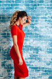 Beautiful young woman in red dress around blue background. royalty free stock photos