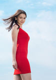 Beautiful young woman in red dress & blue sky Royalty Free Stock Image