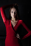Beautiful young woman in red dress - dark room Stock Photos