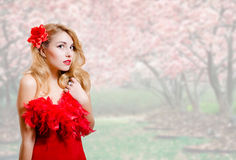 Beautiful young woman in red dress on garden Stock Images