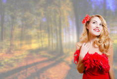 Beautiful young woman in red dress on garden Stock Photos