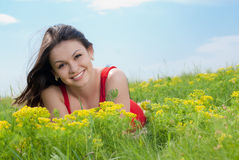 Beautiful young woman in red dress on grass & sky Stock Images