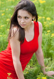 Beautiful young woman in red dress on green grass Stock Photo