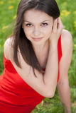 Beautiful young woman in red dress & green grass Stock Images