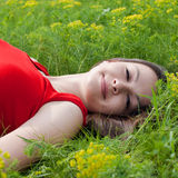 Beautiful young woman in red dress & green grass Royalty Free Stock Photos