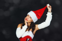 Beautiful young woman in a red dress and hat of Santa Claus on a black background Royalty Free Stock Photography