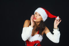Beautiful young woman in a red dress and hat of Santa Claus on a black background Royalty Free Stock Photos