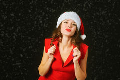 Beautiful young woman in a red dress and hat of Santa Claus on a black background Stock Photos