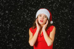 Beautiful young woman in a red dress and hat of Santa Claus on a black background Stock Image