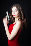 Beautiful young woman in red dress holding gun Stock Images
