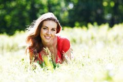 Young woman in red dress lying on grass Royalty Free Stock Photography
