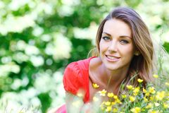 Young woman in red dress lying on grass Royalty Free Stock Photos