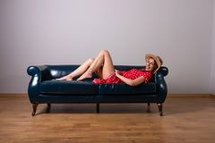 A woman in a red dress posing on the sofa. A beautiful young woman in a red dress lying and posing on a sofa royalty free stock photo