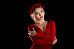 Beautiful young woman in a red dress and a rose wreath Royalty Free Stock Image