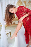 Beautiful young woman in red dress shaving legs in bathroom Royalty Free Stock Photo