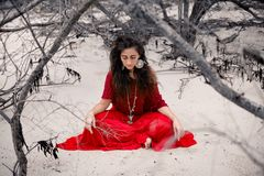 Beautiful young woman in red dress sitting on sand on the beach. Royalty Free Stock Photos