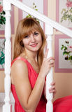 Beautiful young woman in a red dress sitting on stairs Stock Photo