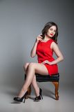 Beautiful young woman in a red dress  spraying the Royalty Free Stock Photo