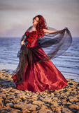 Beautiful young woman in red dress standing on sea coast Royalty Free Stock Photography