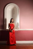 Beautiful young woman red evening dress in gallery Stock Image