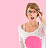 Beautiful young woman with red eyeglasses surprised Royalty Free Stock Image