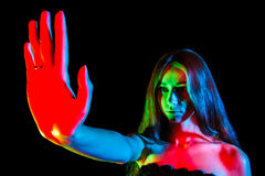 Beautiful young woman in red, green and blue lights showing the Royalty Free Stock Photos