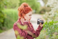 Beautiful young woman with red hair in the garden taking pictures Stock Photography
