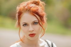 Beautiful young woman with red hair, outside in a park in the sunlight, looking into the camera stock photo