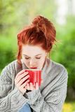 Beautiful young woman with red hair sitting in the garden, relaxing, drinking coffee stock images
