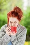 Beautiful young woman with red hair sitting in the garden, relaxing, drinking coffee royalty free stock image