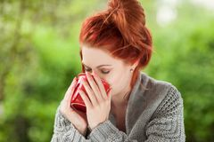 Beautiful young woman with red hair sitting in the garden, relaxing, drinking coffee royalty free stock images