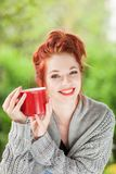 Beautiful young woman with red hair sitting in the garden, relaxing, drinking coffee stock photography