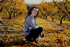 Beautiful young woman posing in an autumn field. Sunny day. Red-haired. Teenager. Beautiful young woman red-haired posing in an autumn field. Trees with oranges stock image