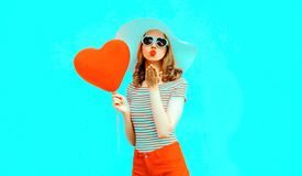 Beautiful young woman with red heart shaped balloons sending sweet air kiss on colorful stock images