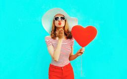 Beautiful young woman with red heart shaped balloons sending sweet air kiss on colorful blue royalty free stock photos