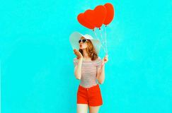 Beautiful young woman with red heart shaped balloons sending sweet air kiss on colorful blue stock photography