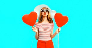 Beautiful young woman with red heart shaped balloons sending sweet air kiss on colorful blue royalty free stock image