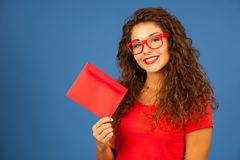 Beautiful young woman in red holding red envelope.  Stock Image