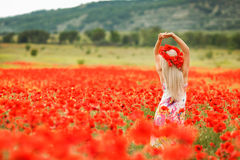 Beautiful young woman in red light poppy field Royalty Free Stock Image