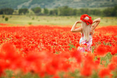 Beautiful young woman in red light poppy field Stock Image