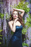 Beautiful young woman with red lips in the sprakling blue dress Royalty Free Stock Photos