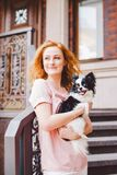 A beautiful young woman with red long hair is holding a small, cute funny big-eyed dog of two flowers, a black-and-white pet of th Stock Image