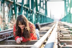 Beautiful Young Woman Lying Down on the Train Tracks stock image