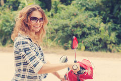 Beautiful young woman on a red motorbike Stock Photo