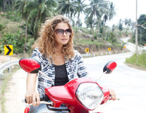 Beautiful young woman on a red motorbike Stock Photos