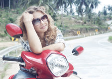 Beautiful young woman on a red motorbike Stock Image