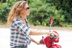 Beautiful young woman on a red motorbike Stock Photography