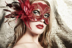 Beautiful young woman in a red mysterious mask Royalty Free Stock Photos