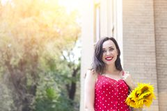 Beautiful young woman in red polka dots dress holding basket with sunflowers. Close up stock photography